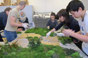 Das Bild zeigt Jugendliche beim Bau einer Mooswand.